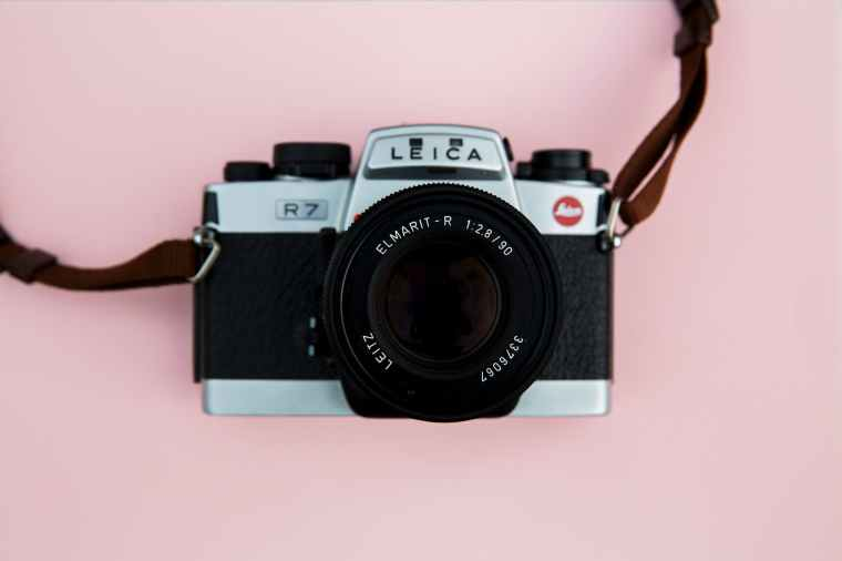 black and grey leica camera on pink background